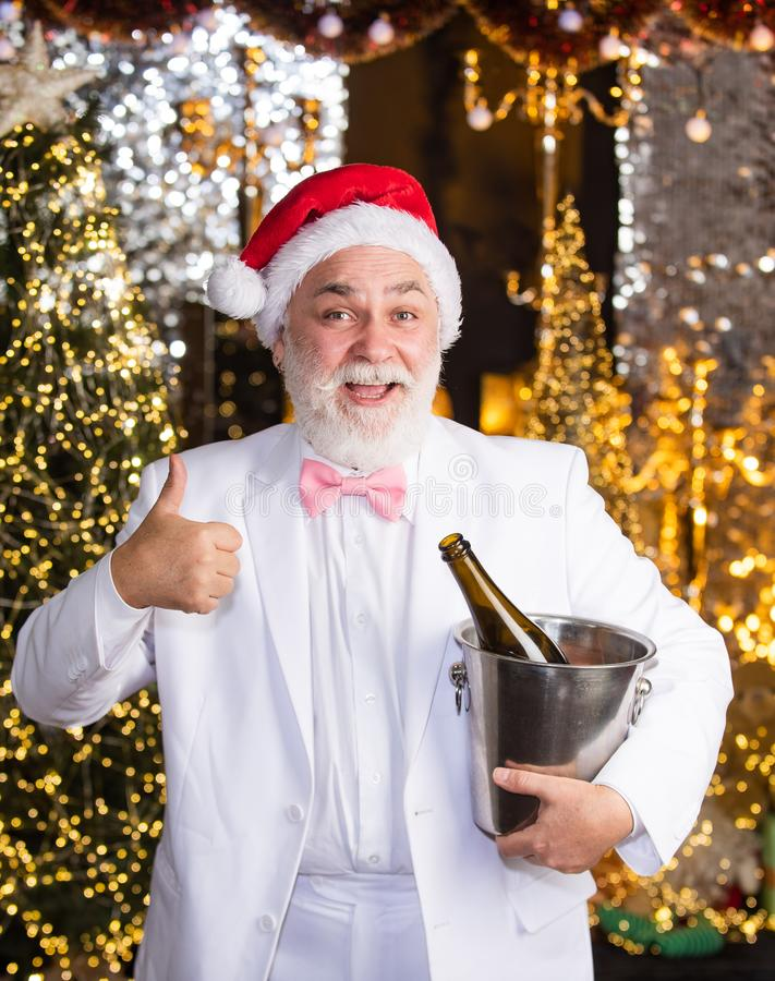 Thank you. tuxedo senior sommelier. new year night might be long. merry christmas to you. lets celebrate. cheerful man. Hold ice bucket with champagne bottle stock photo