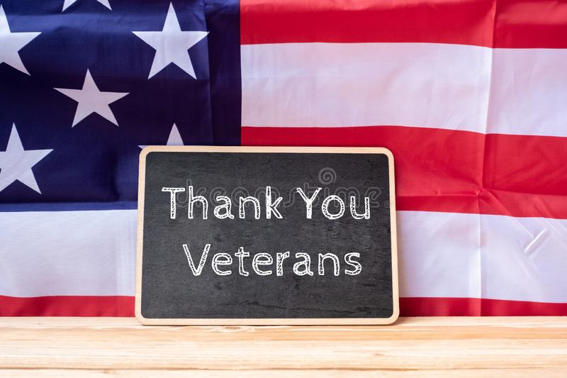 Thank You Veterans text written in chalkboard with flag of the United States of America on wooden background. stock photos