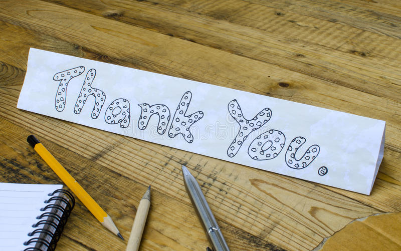 Thank you wording on paper. On wooden background royalty free stock photography