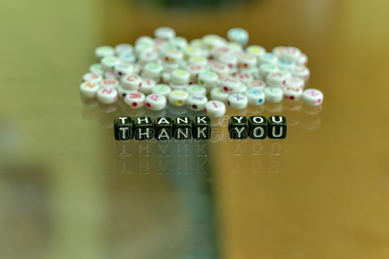 THANK YOU  written with Acrylic Black cube with white Alphabet Beads on the Glass Background. THANK YOU written with Acrylic Black cube with white Alphabet Beads stock image
