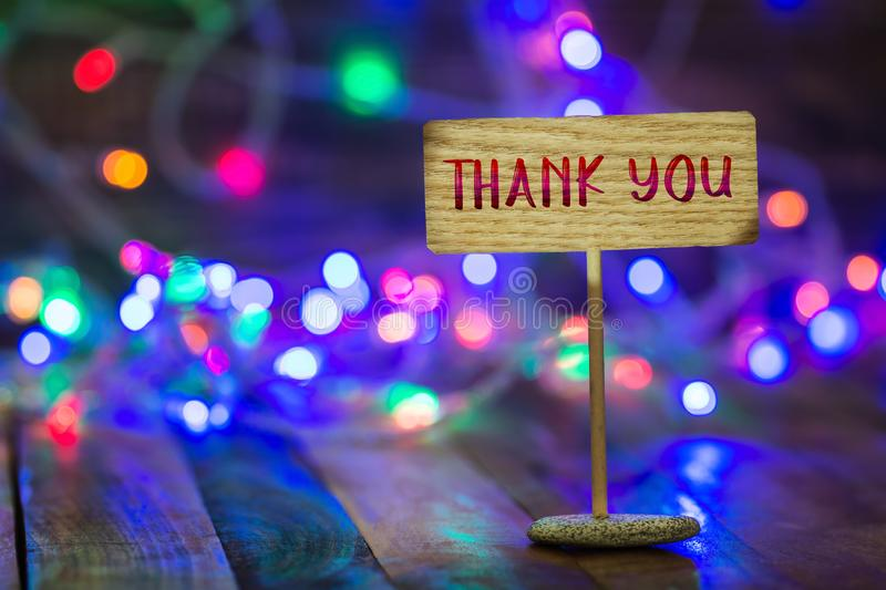 Thank you on small sign board. Thank you written on small wooden sign board on wooden table with Christmas light and bokeh background stock photography