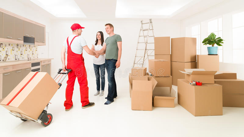 Thank you for your service. Couple moving in new home and receiving package from delivery man royalty free stock images