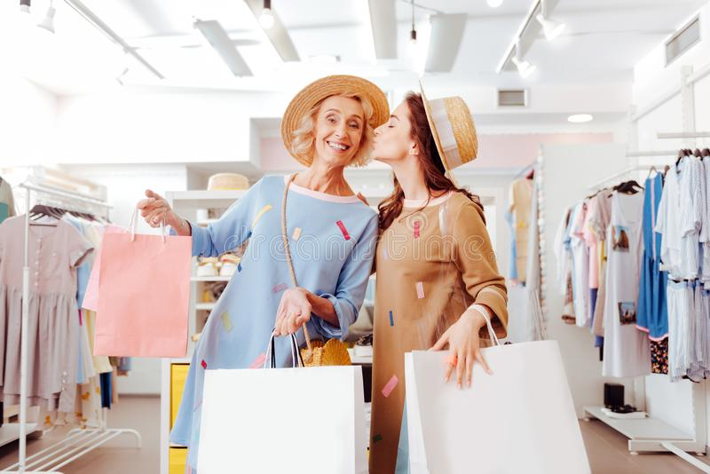 Fashionable daughter thanking her mother for shopping time royalty free stock photos