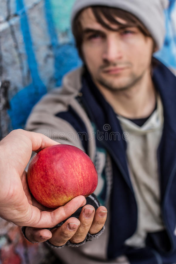 Thankful eyes of homeless man. Getting food. Kind stranger gives apple to homeless man royalty free stock image