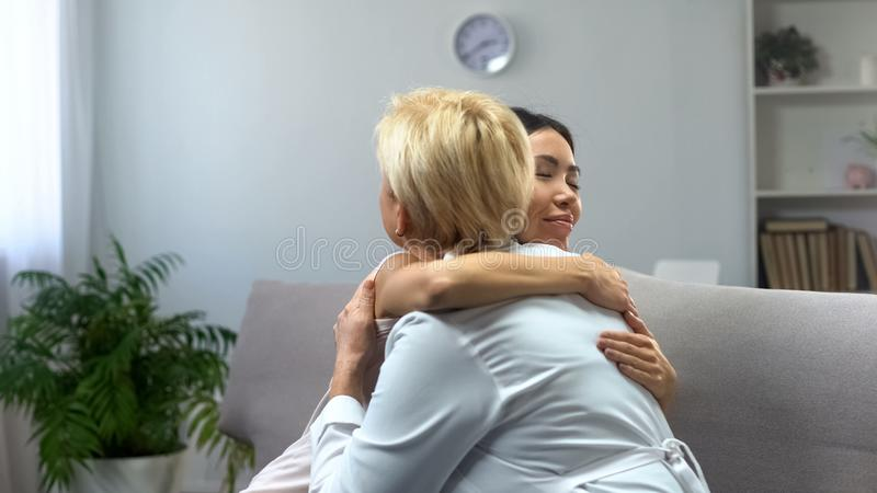 Thankful girl hugging female doctor, cancer remission, cure after treatment royalty free stock photography