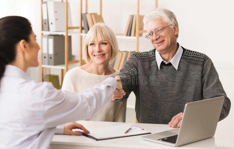 Thankful senior patient shaking hands with doctor royalty free stock images