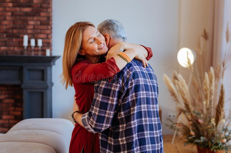 Thankful beaming wife hugging her supportive loving husband. Thankful wife. Thankful beaming wife wearing red dress hugging her supportive loving husband royalty free stock photo