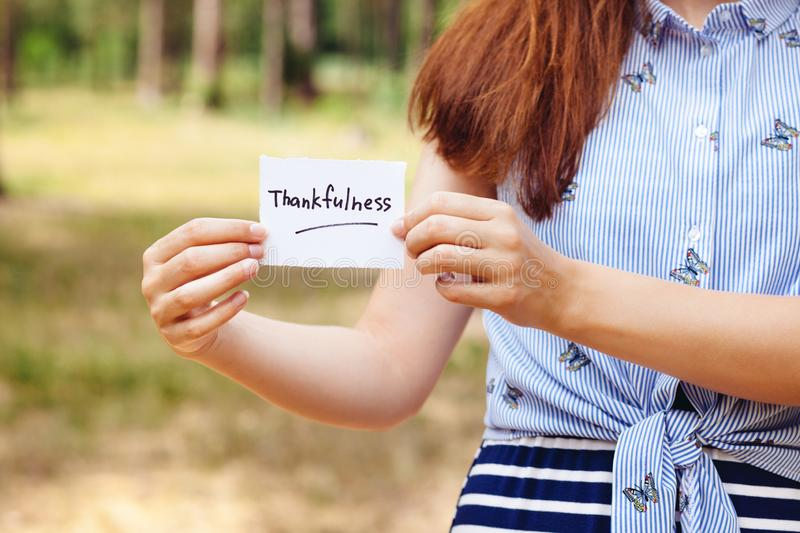Thankfulness - woman and text on paper on nature background, religion and thanksgiving concept stock photo