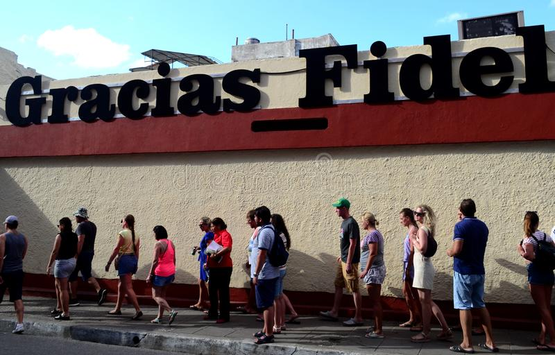 Thanks Fidel! Tourists in Santa Clara, Cuba. Tourism, walk, wall, revolution, che, guevara, castro, gracias, accent, lifestyle, cityscape royalty free stock image