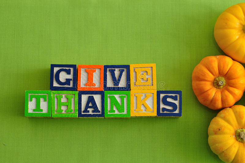 Thanks giving day. Give thanks in colorful blocks displayed with pumpkins royalty free stock photography