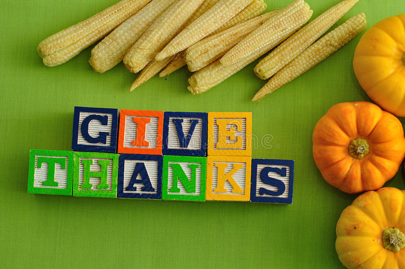 Thanks giving day. Give thanks spelled with Alphabet blocks with corn and pumpkins against a green background stock images