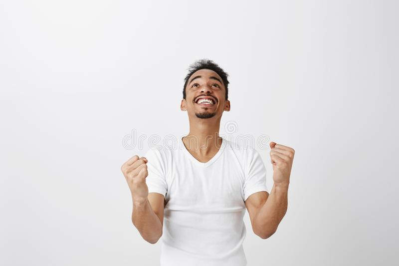 Thanks god I passed exams. Overwhelmed excited young man in casual white t-shirt, raising clenched fists and looking up stock image