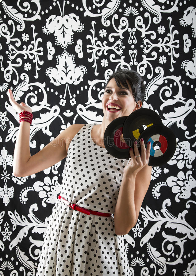 Thanks the heaven for records. Young woman with stylist clothes, with a happy expression at three small record royalty free stock photo