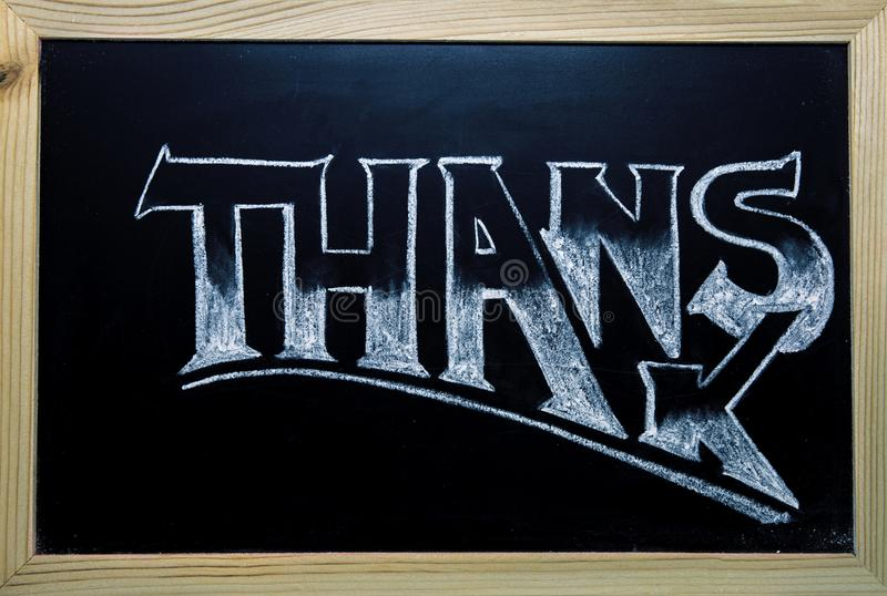 Thanks inscription by white chalk on black chalkboard. Thanks word in timber frame. Shop or cafe customer thanks banner. Thanks lettering in classic serif stock image