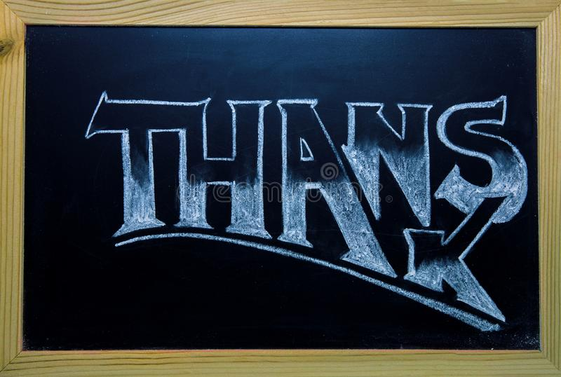 Thanks inscription by white chalk on black chalkboard. Thanks word in wooden frame. Shop or cafe customer thanks banner. Thanks lettering in classic serif royalty free stock photography