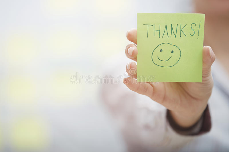 Thanks text on adhesive note. Woman holding sticky note with Thanks text royalty free stock photos