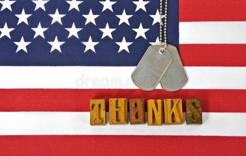 Thanks to military. Military dog tags and word thanks in vintage wooden letterpress type on American flag stock photo