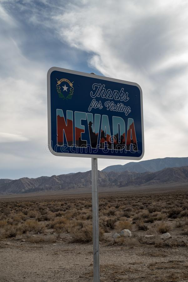 Thanks for visiting Nevada road sign in desert landscape. With mountains leaving the state of Nevada and heading into California, USA royalty free stock image