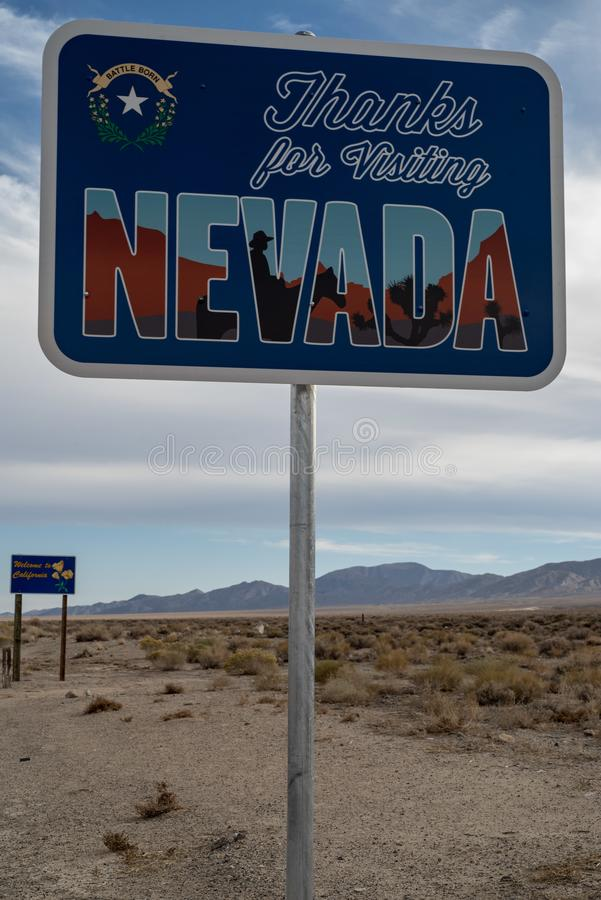 Thanks for Visiting Nevada road sign in desert with mountains. Thanks for Visiting Nevada road sign in desert at the state line into California, USA royalty free stock photo