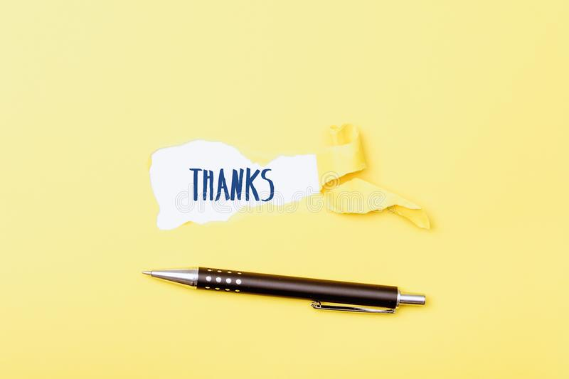 Thanks written on paper revealed by ripped piece. Thanks written in background on ripped pieces of cardboard paper royalty free stock photos