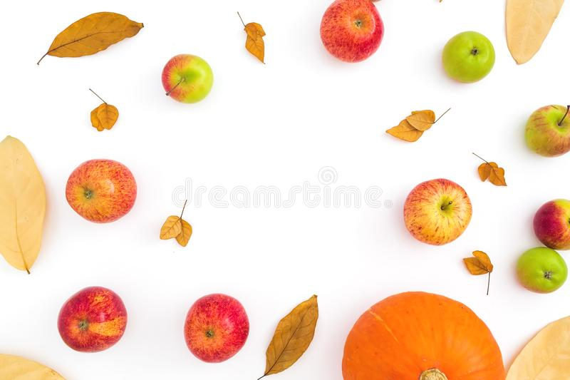 Thanksgiving autumn frame with fall dried leaves, apples and pumpkin on white background. Flat lay, top view stock images