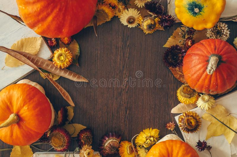 Thanksgiving background with autumn dried flowers, pumpkins and fall leaves on the old wooden background. Abundant harvest concept stock photography