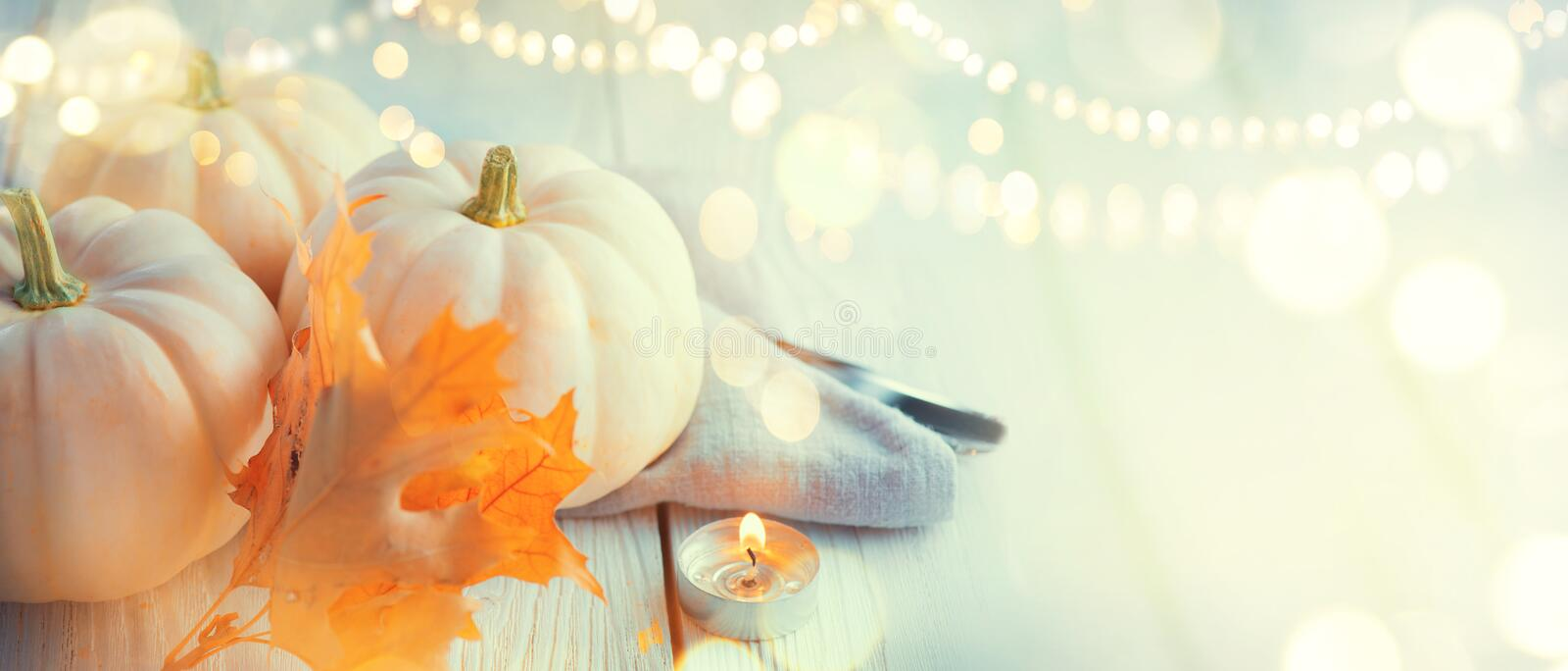 Thanksgiving background. Wooden table, decorated with pumpkins, autumn leaves and candles royalty free stock photography