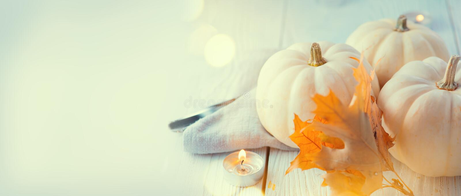 Thanksgiving background. Wooden table, decorated with pumpkins, autumn leaves and candles stock image