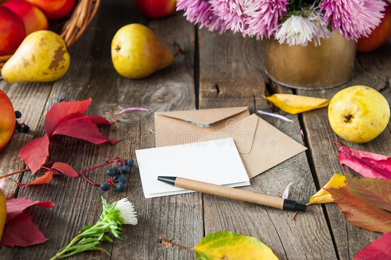 Thanksgiving background with seasonal fruits, flowers, greeting card and few craft envelopes on a rustic wooden table. Autumn harv stock image