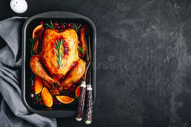 Thanksgiving baked chicken or turkey with spices, oranges and cranberries. On dark concrete stone background stock photography