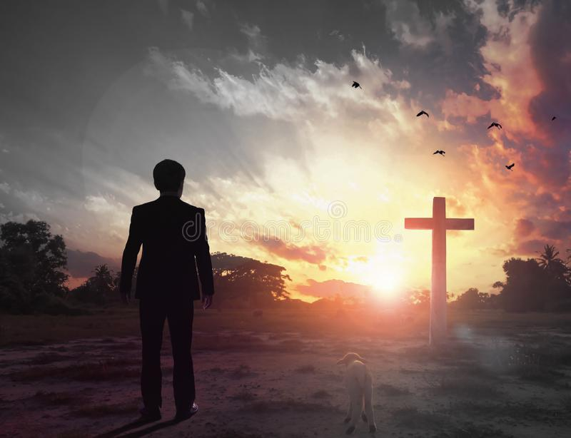 Thanksgiving concept: a businessman standing in front of the cross stock photo