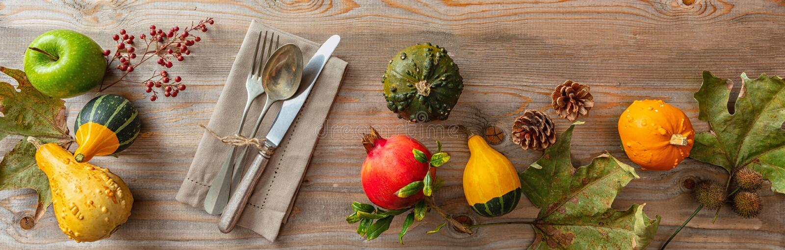 Thanksgiving flat lay with colorful pumpkins and place setting on rustic wooden table, banner, top view. Thanksgiving concept. Colorful pumpkins and place stock photo