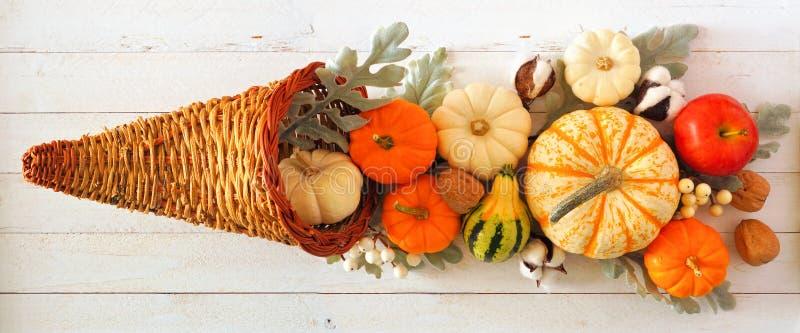 Thanksgiving cornucopia gevuld met herfstpompoenen en groenten, bovenaanzicht tegen wit hout royalty-vrije stock afbeelding