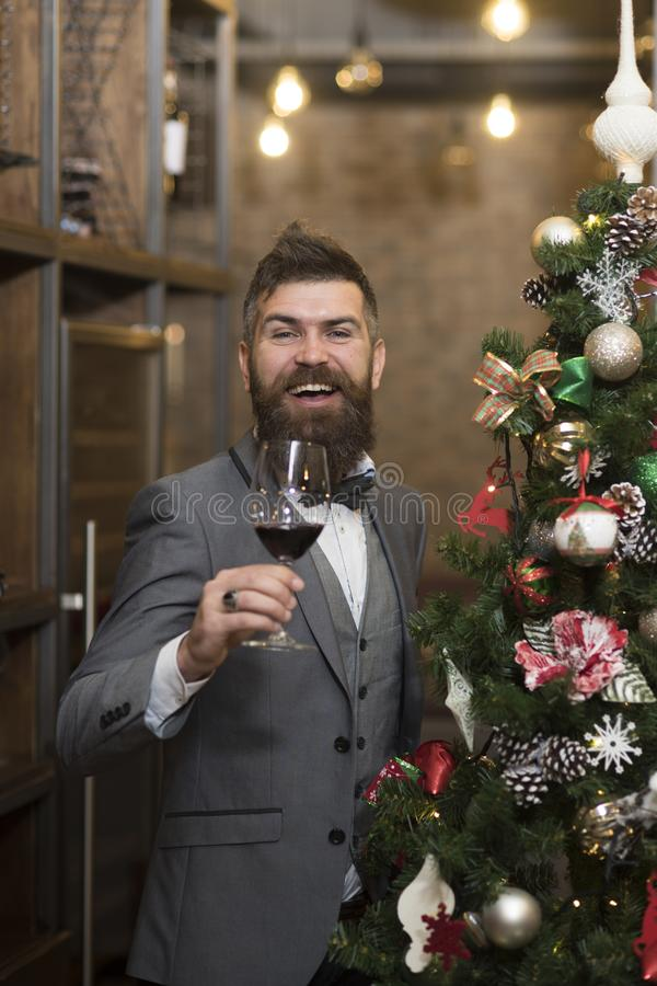 Thanksgiving Day greeting toast of guy. Thanksgiving day with happy bearded man holding wine glass at new year tree royalty free stock images