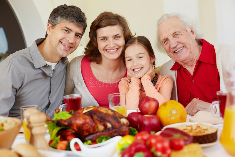 Thanksgiving day. Happy family of four sitting at festive table on Thanksgiving day stock photo