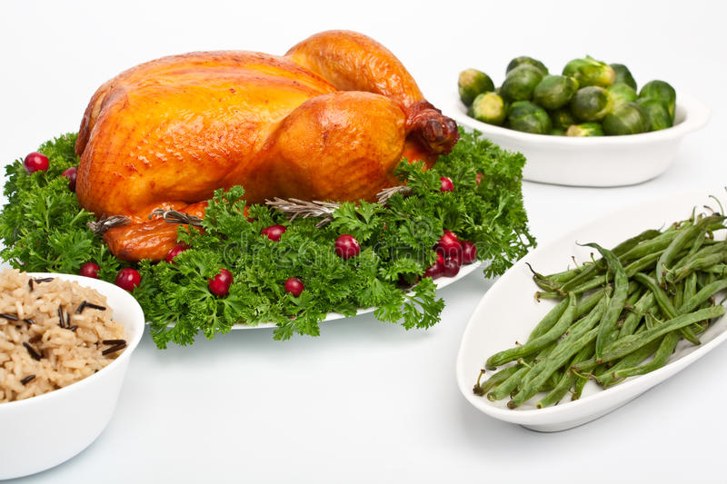 Thanksgiving dinner. Whole roasted chicken with parsley and cranberries on a dish, rice, green beens and Brussels sprouts stock image