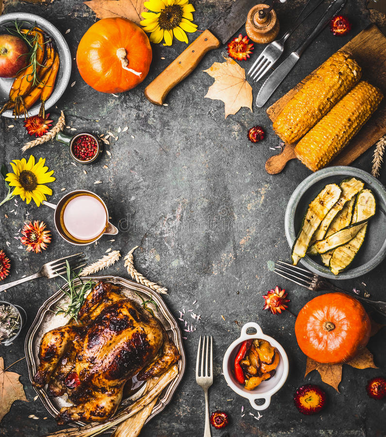 Thanksgiving dinner background with roasted turkey , sauce , pumpkin and dishes of autumn vegetables on rustic background, top vi stock photography