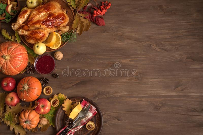 Thanksgiving dinner background. With turkey, fall leaves, seasonal autumnal decor and table setting, top view, copy space royalty free stock photography