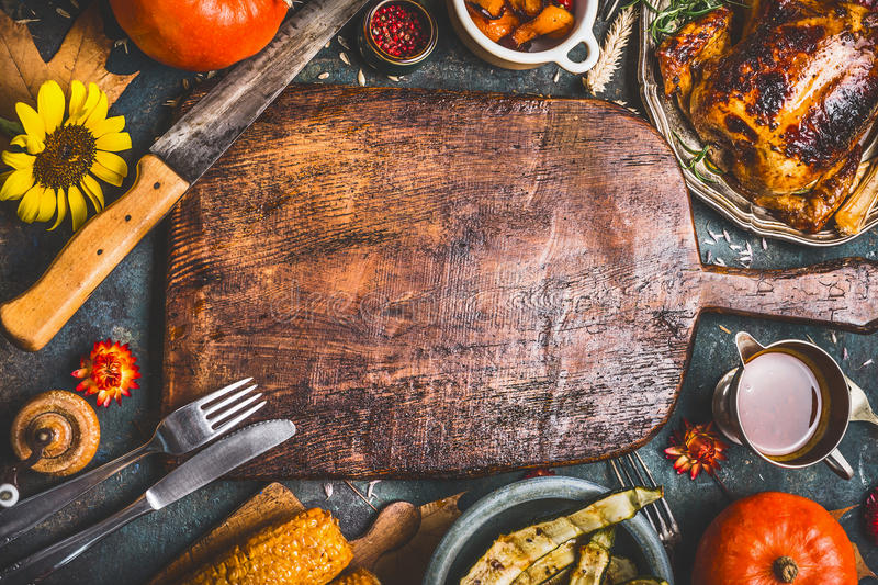 Thanksgiving dinner background with turkey ,sauce,grilled vegetables,corn ,cutlery , pumpkin, fall leaves and flowers arrangemen stock photography