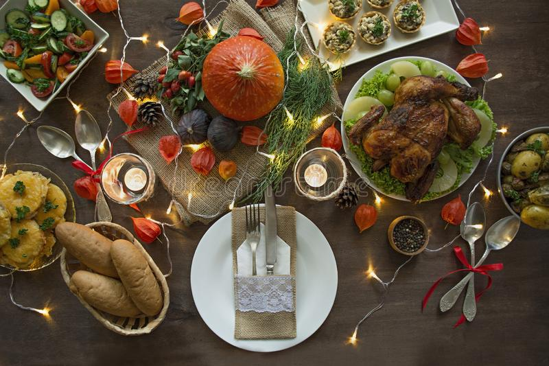 Thanksgiving dinner. Halloween dinner. Festive table with chicken and all side dishes, pumpkin, autumn leaves and seasonal autumn royalty free stock images