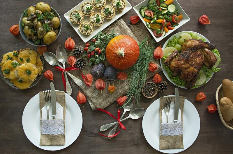 Thanksgiving dinner. Halloween dinner. Festive table with chicken and all side dishes, pumpkin, autumn leaves and seasonal autumn royalty free stock photos