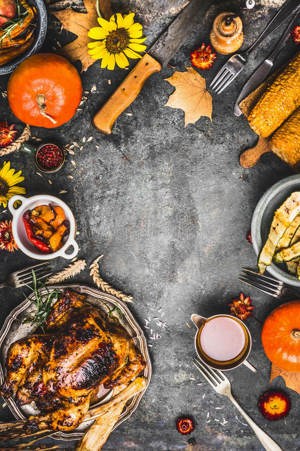 Thanksgiving dinner preparation. Roasted whole chicken or turkey ,sauce with grilled autumn vegetables,corn ,cutlery , decoration stock photography