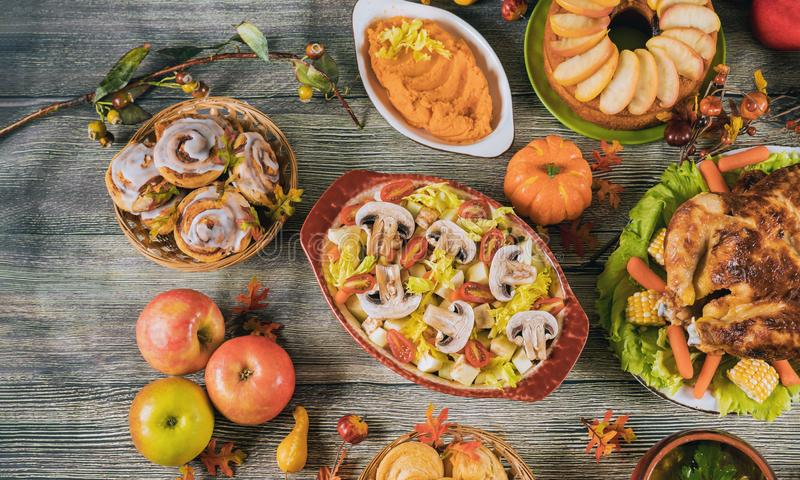 Thanksgiving dinner served with turkey, decorated with autumn leaves and pumpkin. Thanksgiving dinner served with turkey, apples, sweet potato, decorated with stock images