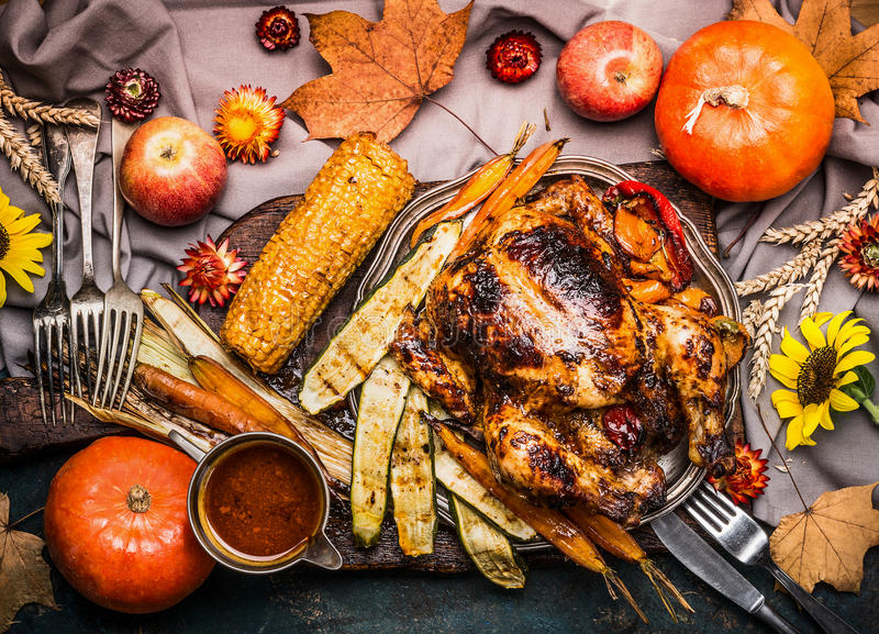 Thanksgiving dinner table with Roasted whole turkey ,sauce with grilled autumn vegetables,corn ,cutlery , decoration pumpkin, autu stock photos