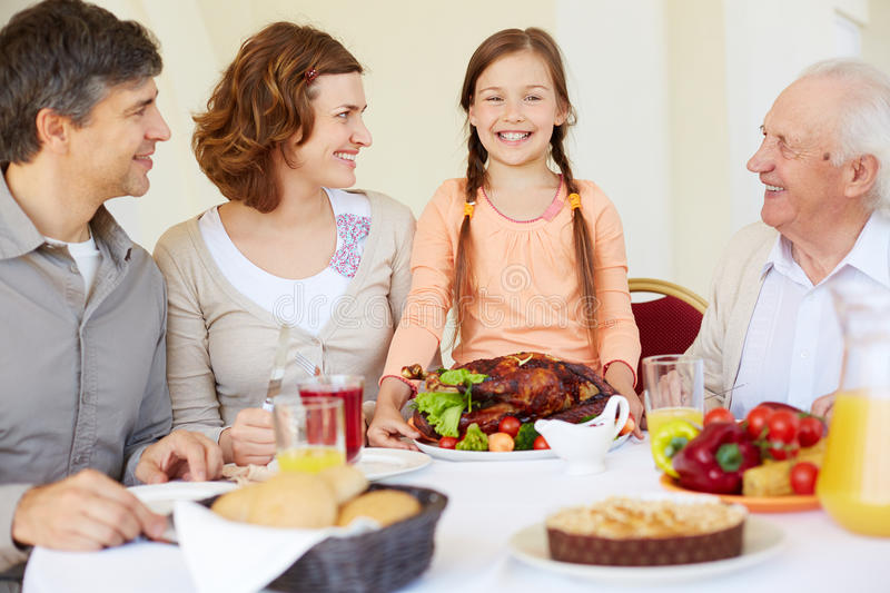 Thanksgiving dish. Portrait of happy family looking at joyful girl during Thanksgiving dinner stock photo