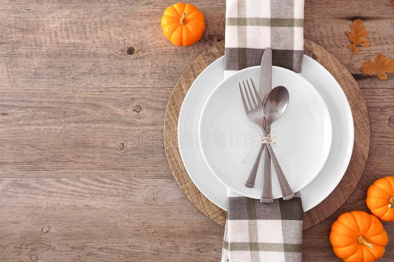 Thanksgiving or fall harvest table setting, top view, side border against a wood background. Thanksgiving or fall harvest table setting with plate, silverware royalty free stock photo