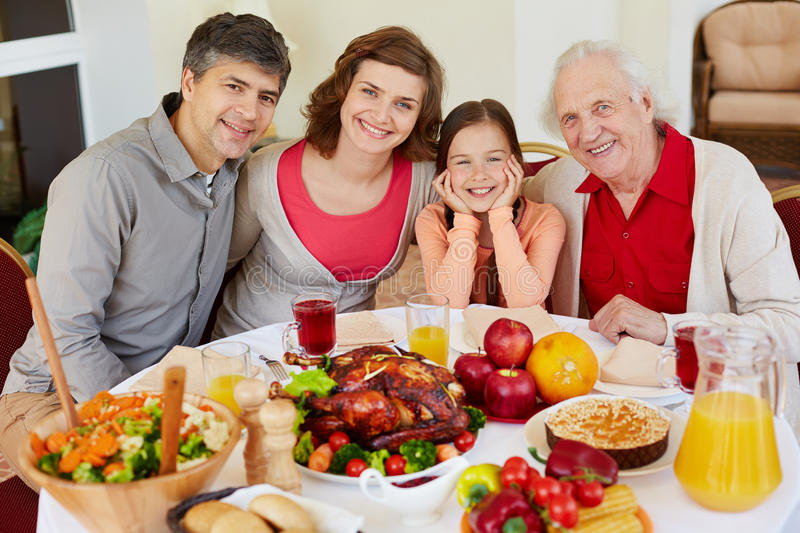 Thanksgiving festivity. Portrait of happy family sitting at festive table on Thanksgiving day royalty free stock images
