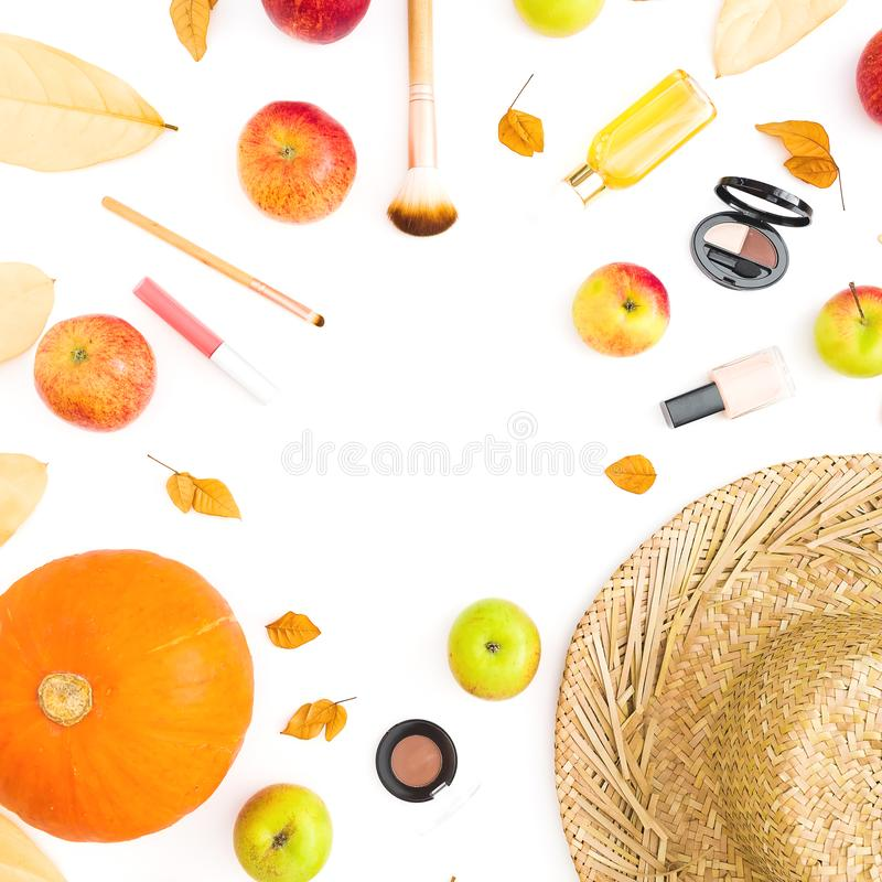Thanksgiving frame of fall leaves, feminine cosmetics and apple and pumpkin on white background. Flat lay, top view stock photos