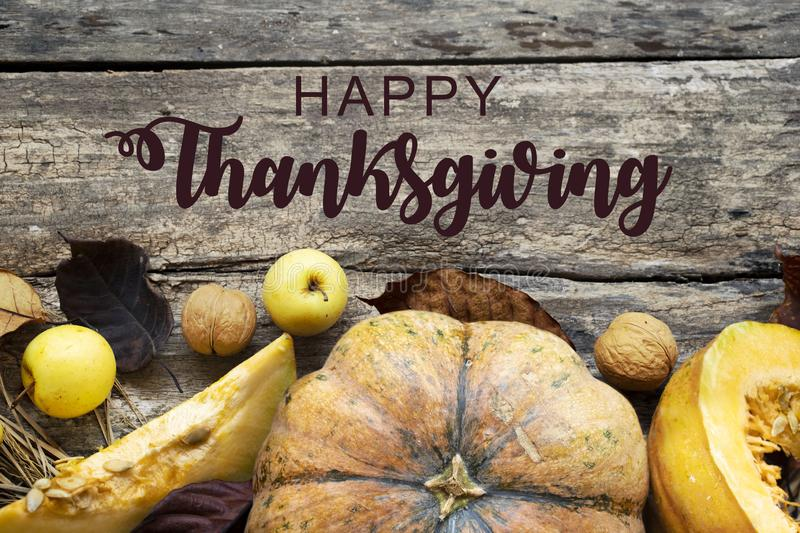 Thanksgiving Greetings. Autumn composition with dry leaves and ripe pumpkins on a dark wooden table. Top view. Flat royalty free stock photo