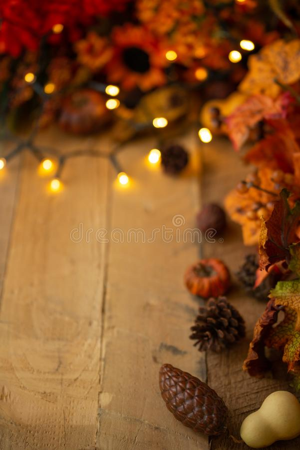 Thanksgiving or Halloween, Autumn composition with dry leaves and small pumpkins on an old wooden table with glowing lights. View stock photo